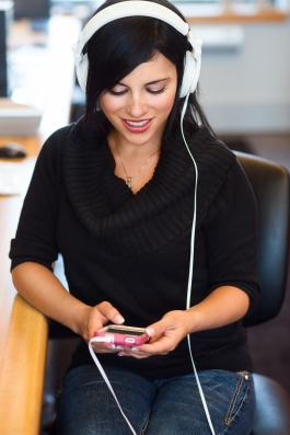 Young woman with headphones looking down at her phone
