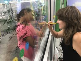 2019 Hadley ideaLAB Maker in Residence Catherine Nelson drawing on lab windows with help from a customer