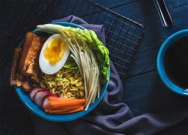 Photo of a plate of food with a hard-boiled egg, sprouts, and greens