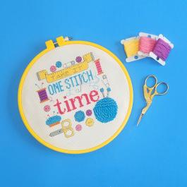 "A photo of a colorful cross stitch project that says ""Take it one stitch at a time"", as well as thread and scissors."