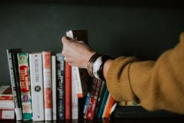 An arm in a yellow sweater with bracelets selects a book from a bookshelf
