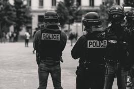 Photo by ev on Unsplash, black and white photo of police officers in riot gear