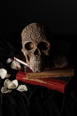 Ornately carved human skull sitting on small stack of books