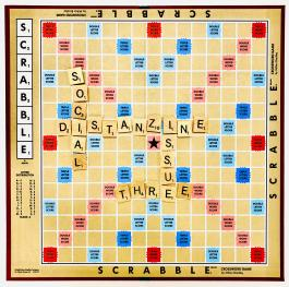 "Scrabble board with pieces that spell out ""social distanzine issue three"""