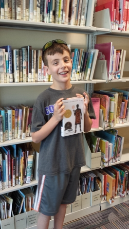 Eli holding one of his favorite Newbery books, The Crossover by Kwame Alexander
