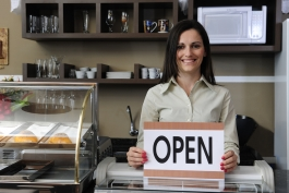 Small business owner holding open sign.