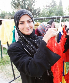 Syrian refugee pictured with clothing she created.