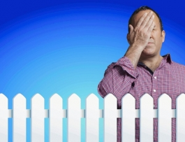 Getty Image - Man smacking his head and standing behind white picket fence.