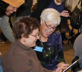 Volunteer Dawn assists a patron learning how to use the iPad.